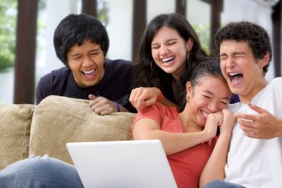 Older teens laughing at computer screen