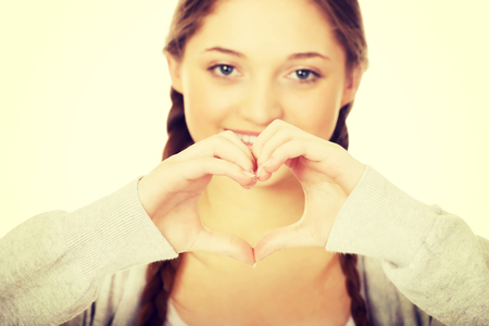49479033 - smiling teen woman making heart shape with her hands.