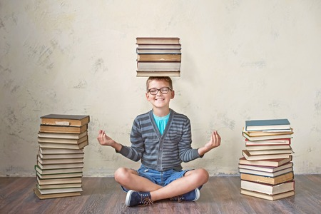 65248710 - the boy student in sneakers shorts and a sweater sitting on a stack of books and reading. on a yellow colored background. educational concept